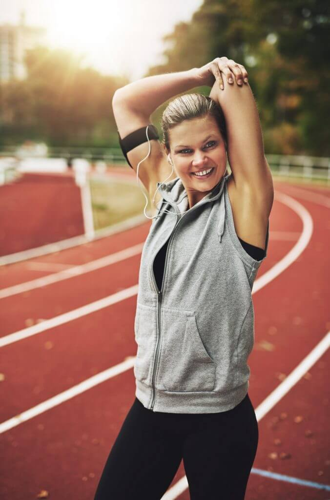 Athletic blonde woman stretching her arms