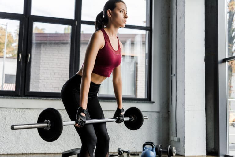beautiful determined sportswoman in weight lifting gloves training with barbell at sports center