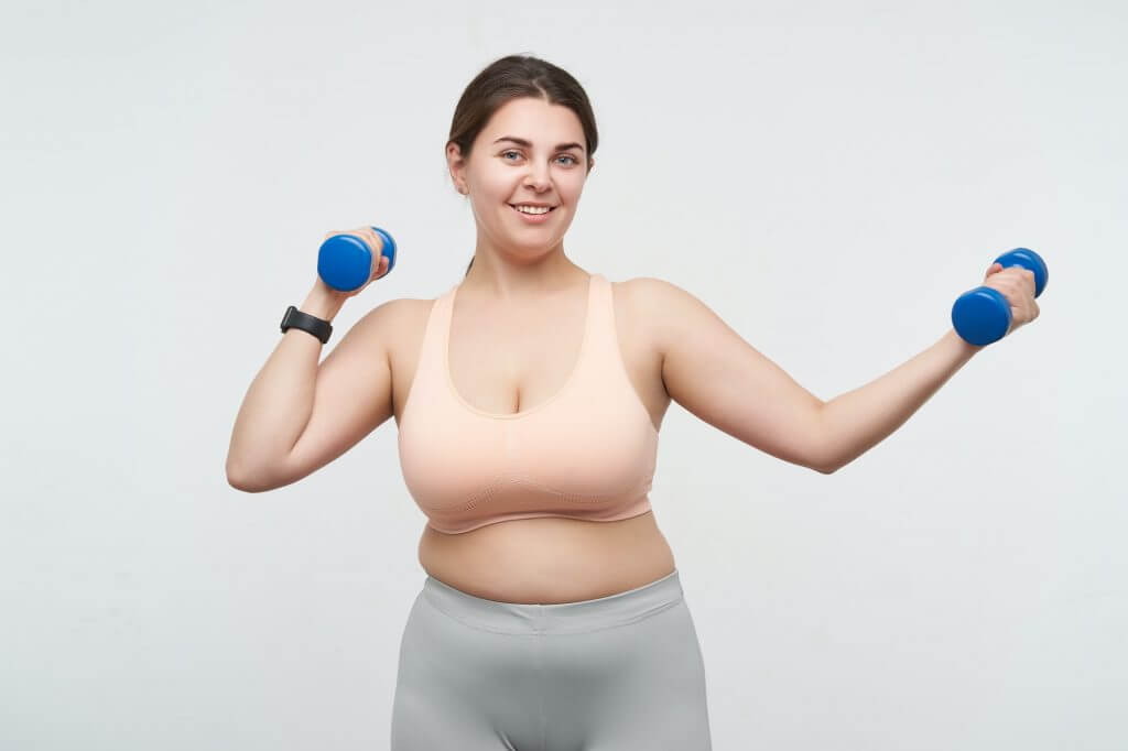 Cheerful young cute oversized woman in sporty clothes smiling nicely at camera while training