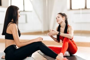 Fitness coach sits with young slim girl on the fitness mat and talk in the fitness room next to the