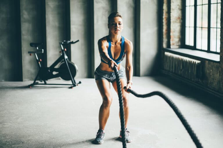 Fitness girl exercising with battle ropes at gym.