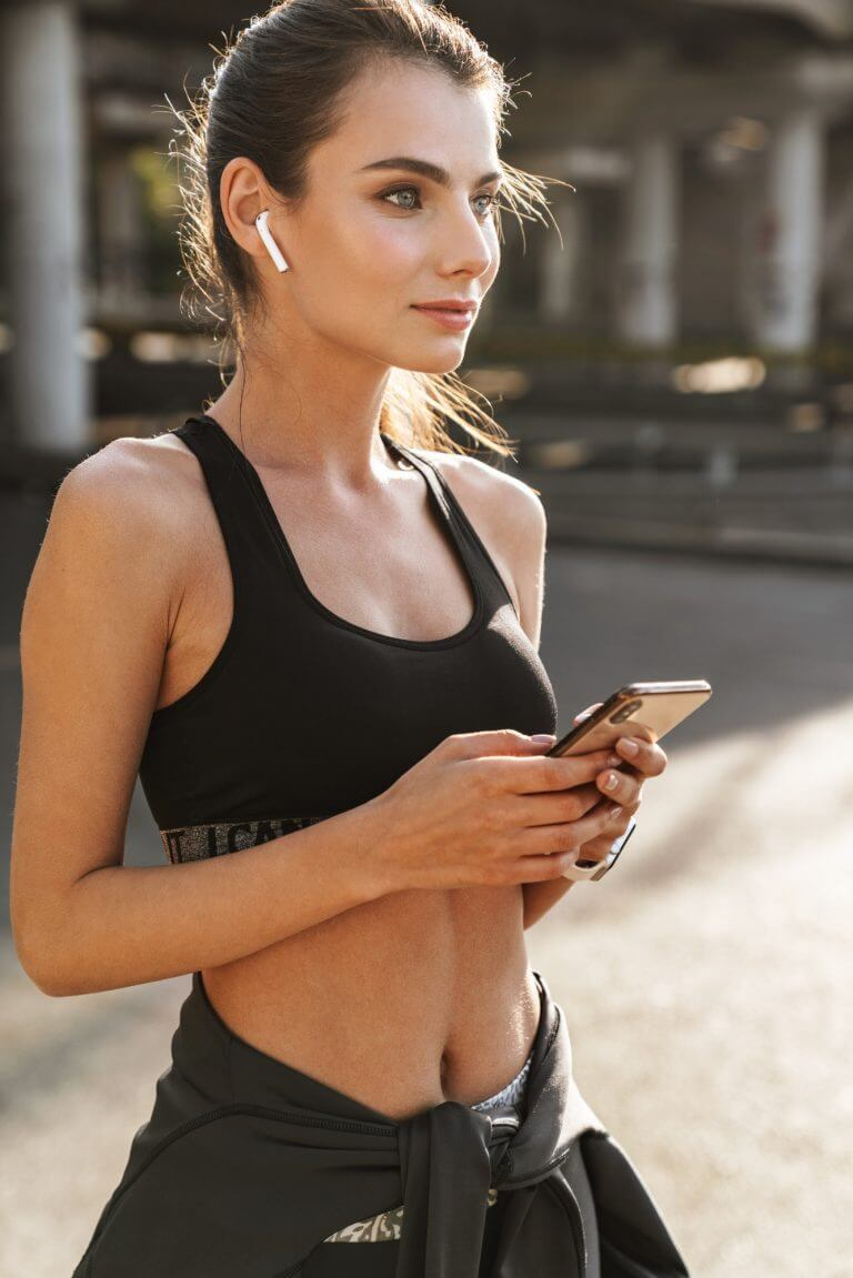 Fitness woman outdoors using mobile phone.