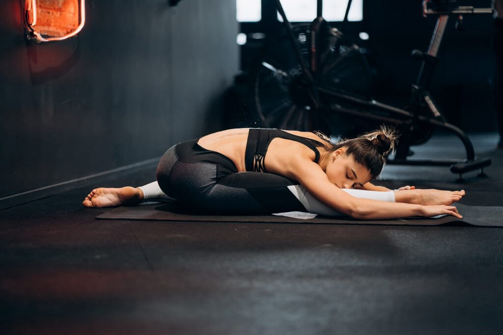 Fitness woman stretching doing pilates stretches exercises