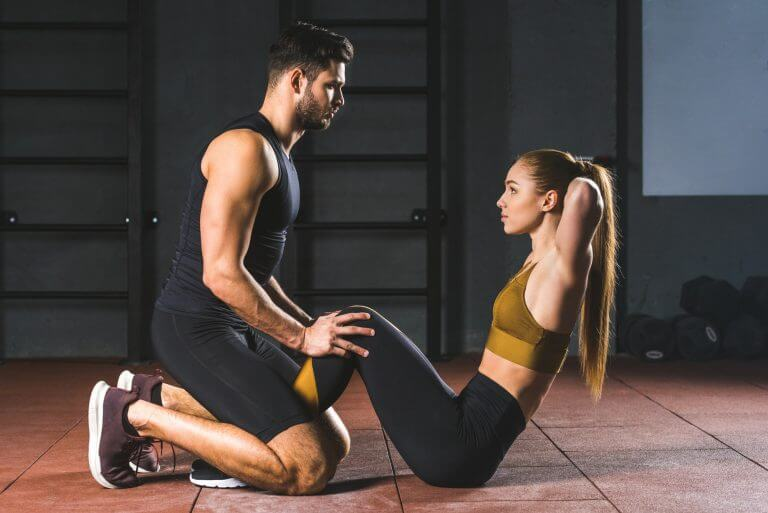 Male coach helping young sportswoman to do abs in sports hall