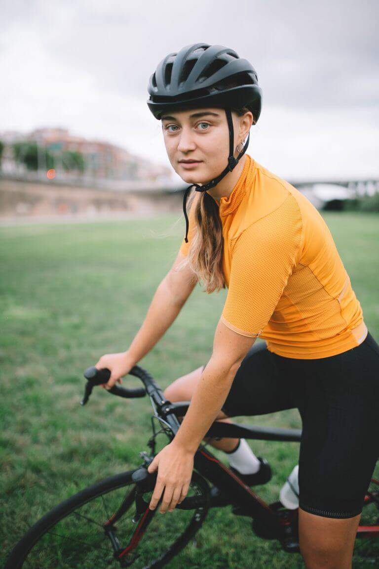 professional cyclist athlete on road bike look at camera and smiles